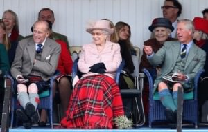 BRAEMAR, SCOTLAND - SEPTEMBER 07: (L-R) Prince Philip, Duke of Edinburgh, Queen Ellizabeth II and Prince Charles, Prince of Wales laugh as they watch the sack race at the annual Braemer Highland Games at The Princess Royal and Duke of Fife Memorial Park on September 7, 2013 in Braemar, Scotland. The Braemar Gathering is the most famous of the Highland Games and is known worldwide. Each year thousands of visitors descend on this small Scottish village on the first Saturday in September to watch one of the more colourful Scottish traditions. The Gathering has a long history and in its modern form it stretches back nearly 200 years. (Photo by Chris Jackson/Getty Images)